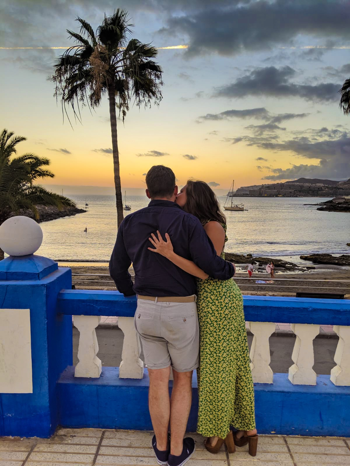 A girl in bright green and yellow dress kissing her boyfriend in the cheek and watching the sun set over the sea in Arguineguin in Gran Canaria