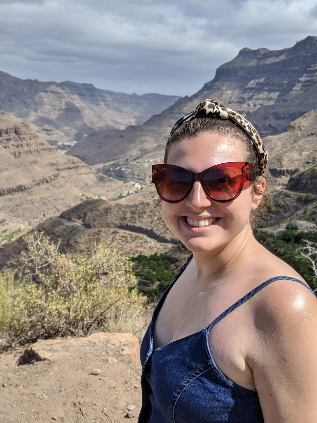 Girl wearing oversized sunglasses and an animal print headband looking directly into the camera with mountains behind her in a small village in gran canaria