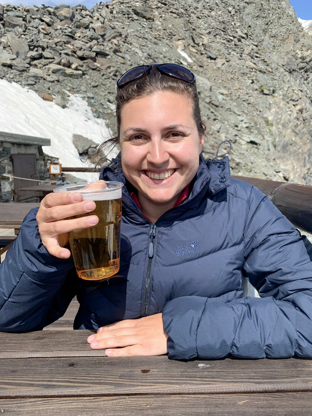 Girl wearing Jack Wolfskin selenium jacket in navy blue, sat outside in the sunshine smiling directly at the camera with a cold pint of beer in her hand. In the background is a stony mountain and some snow.