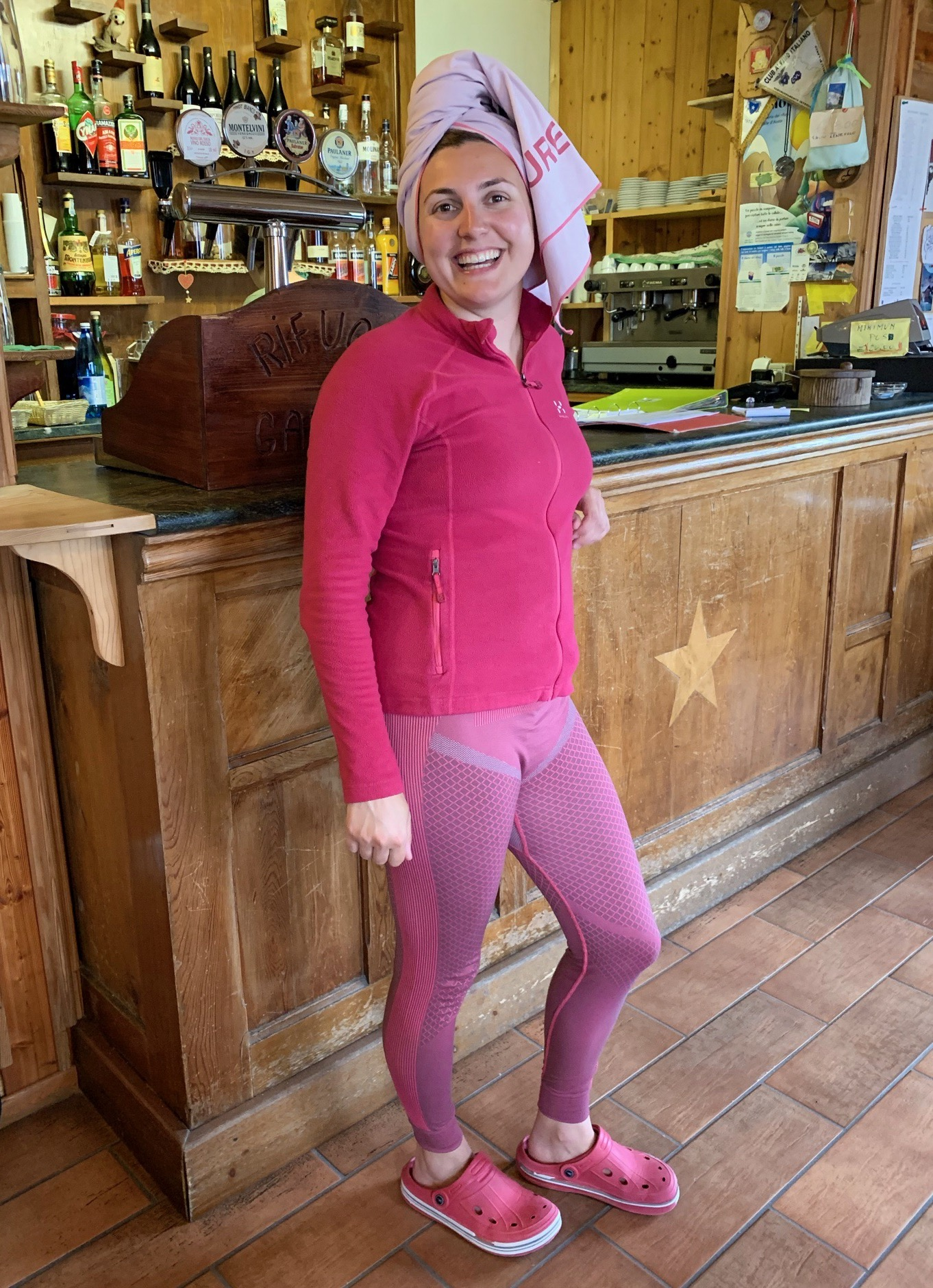 Girl standing in a mountain hut in front of a bar wearing a pink travel towel on her head, pink fleece, pink leggings and pink crocs. She is smiling directly at the camera and laughing. Glacier hiking alps.