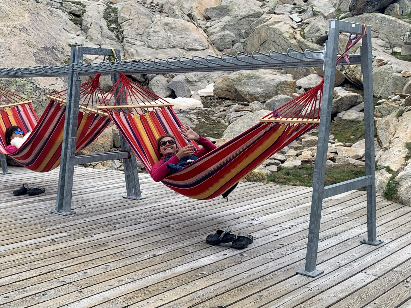 Nell on a brightly coloured hammock with a glass of wine in hand outside the Monte Rosa mountain hut