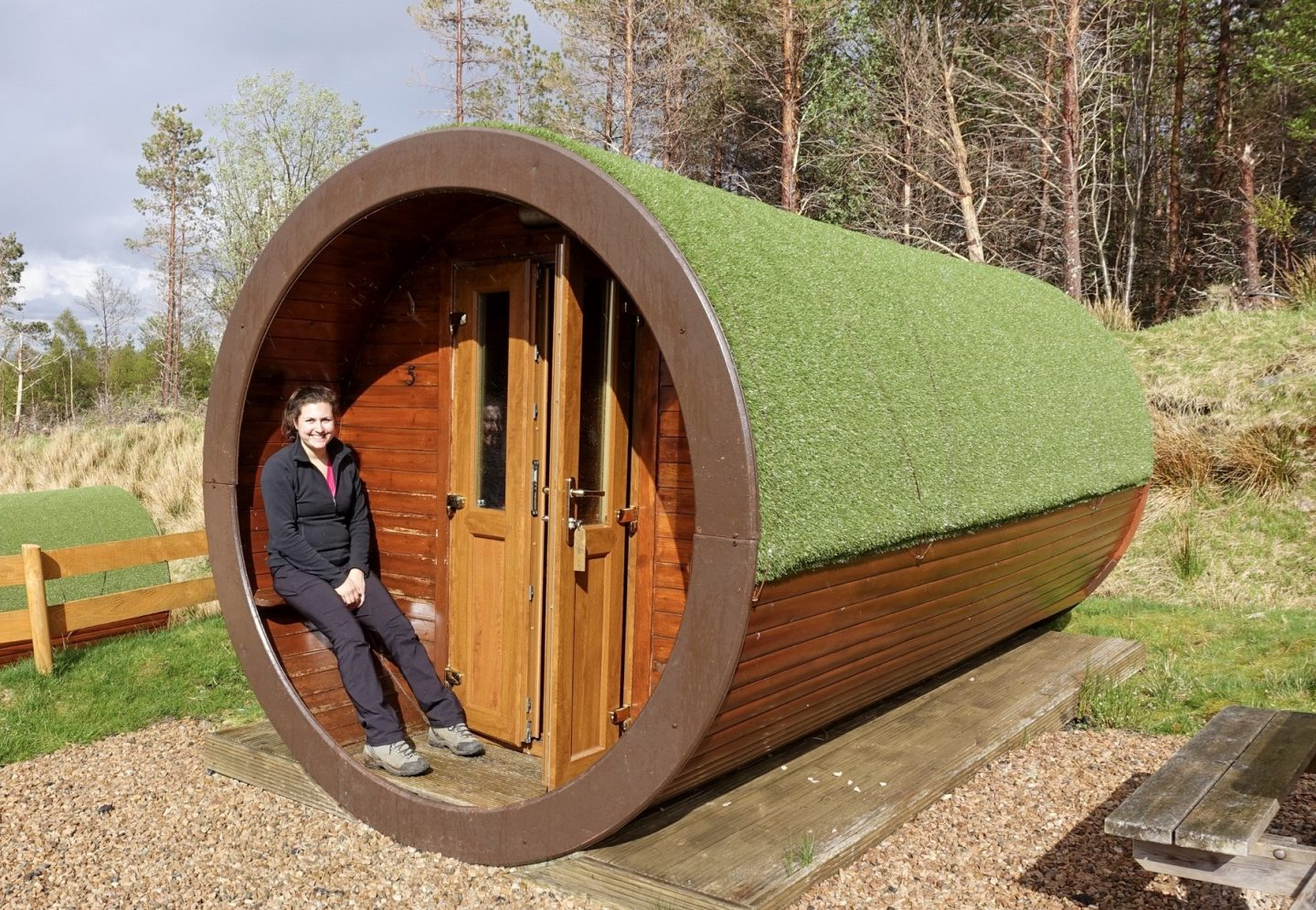 Hobbit house at Glencoe Mountain Resort when walking the west highland way. Nell is sat in the entrance to a wooden tube accommodation covered in green astroturf.