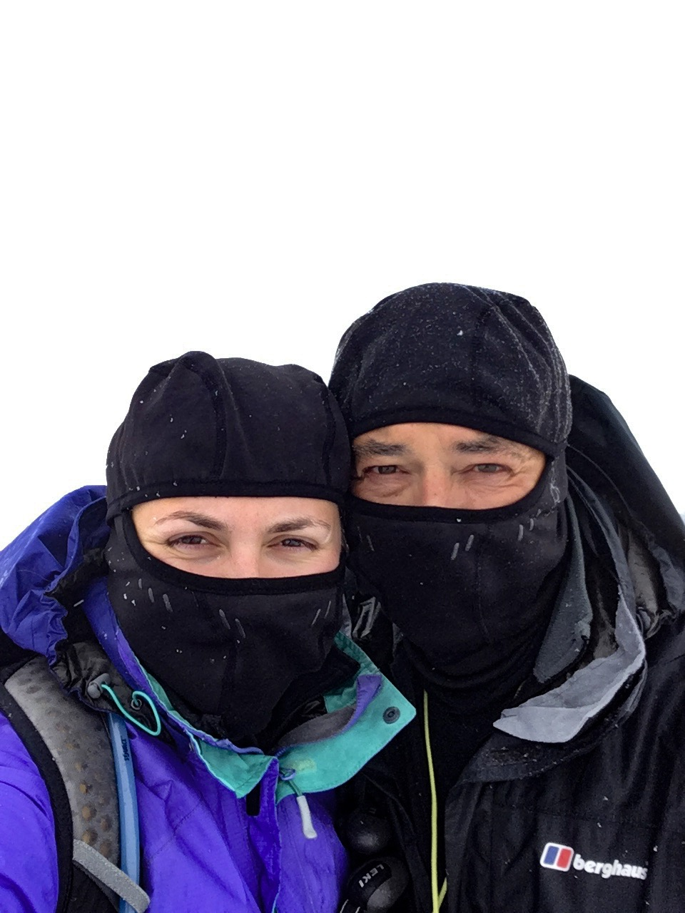 Father and daughter looking very cold at the top of Ben Nevis after walking the West Highland. They are looking directly into the camera but wearing balaclavas and snow is falling on them.