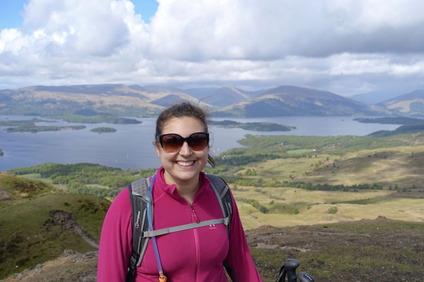 Girl walking the west highland way, wearing a pink fleece and black backpack with scenes of a lake and mountains behind her