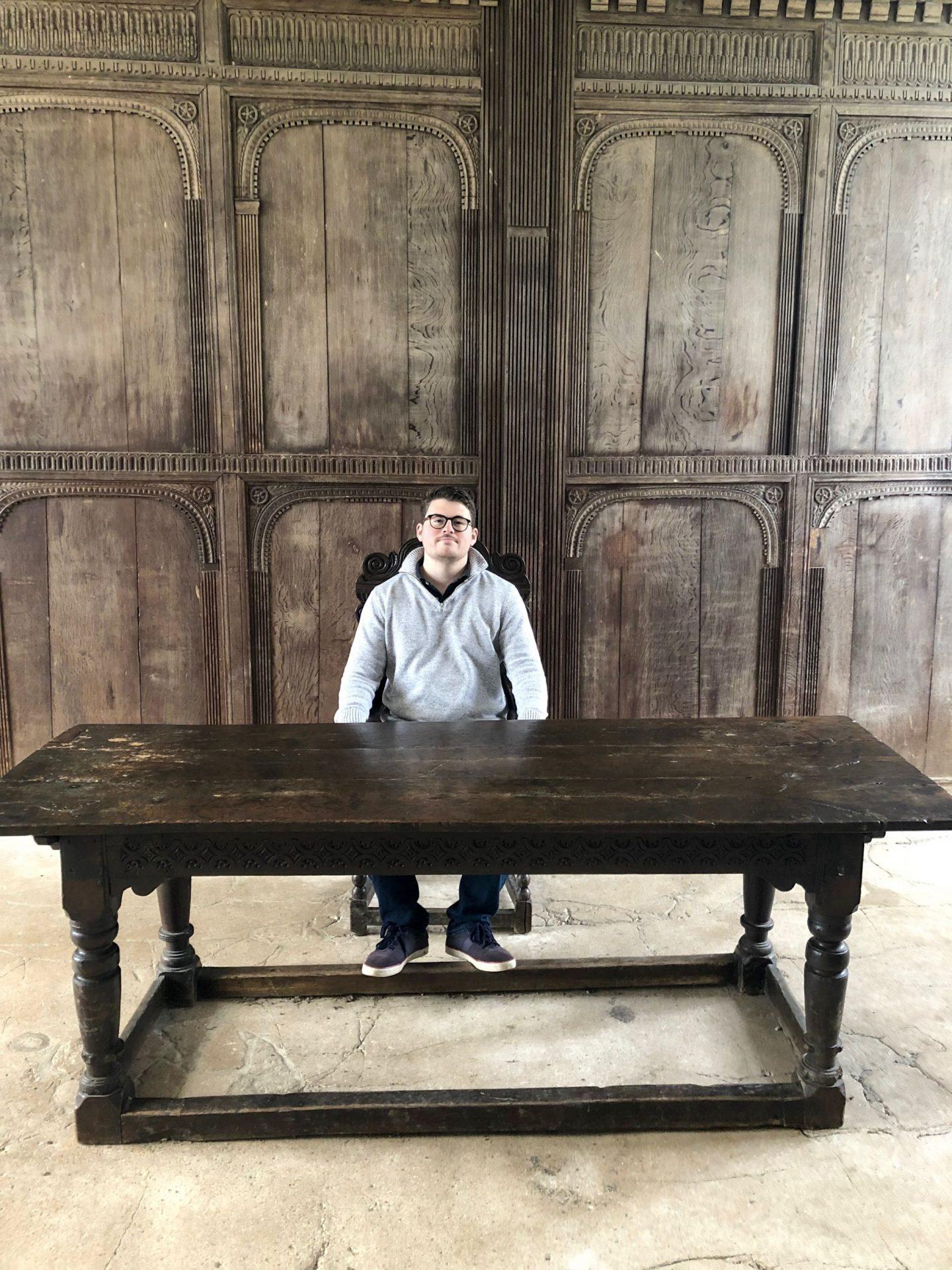 Man sitting at a large wooden desk in Hemlsley castle