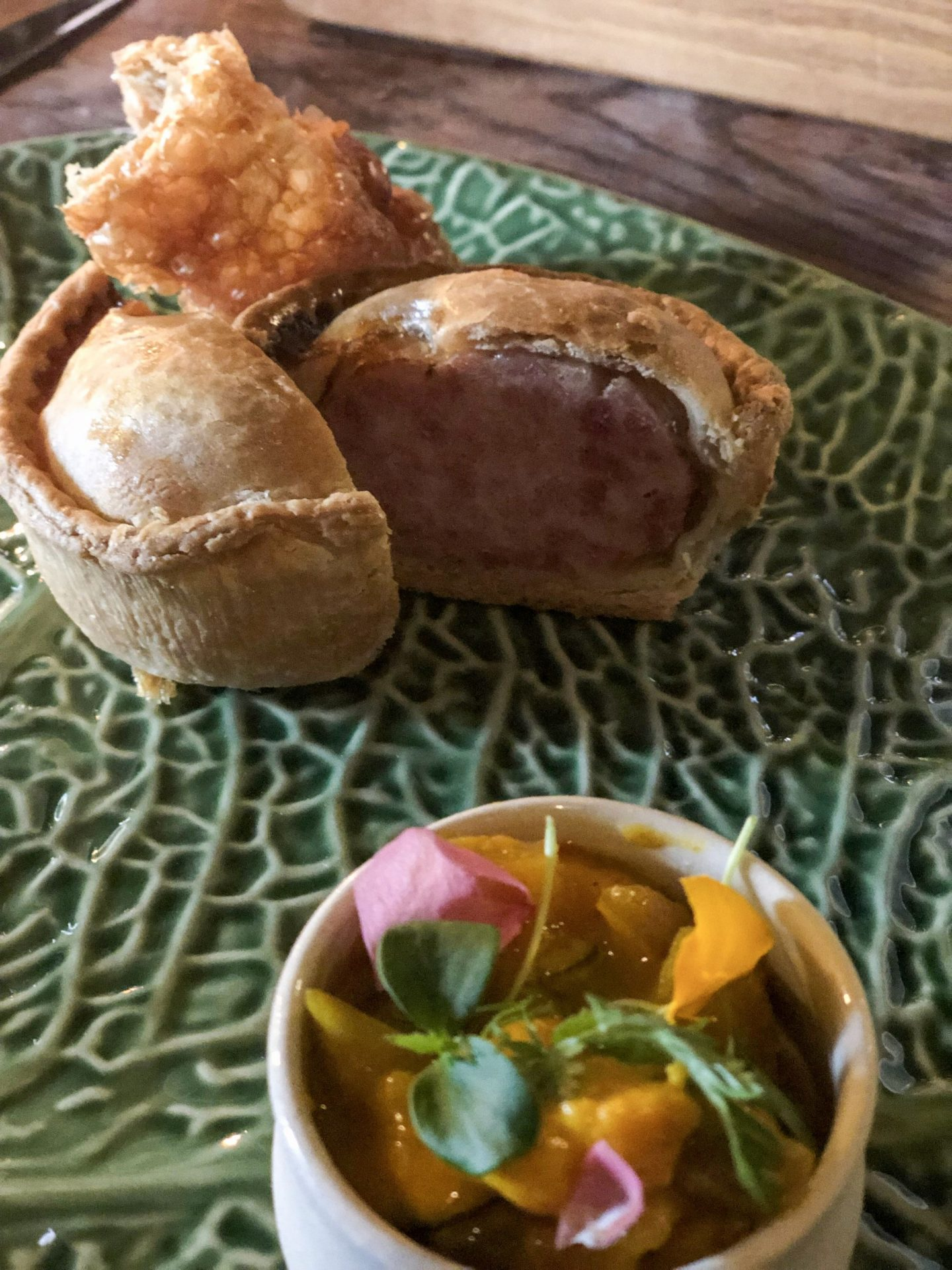 A pork pie cut in half on a green plate, with a vibrant piccalilli in front. Eaten at the Star Inn in Harome, nearby Helmsley