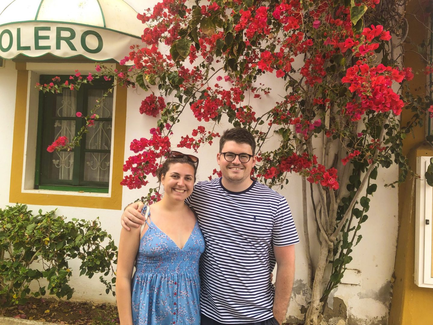 man and women stood in front of bright red flowers in puero mogan in gran canaria