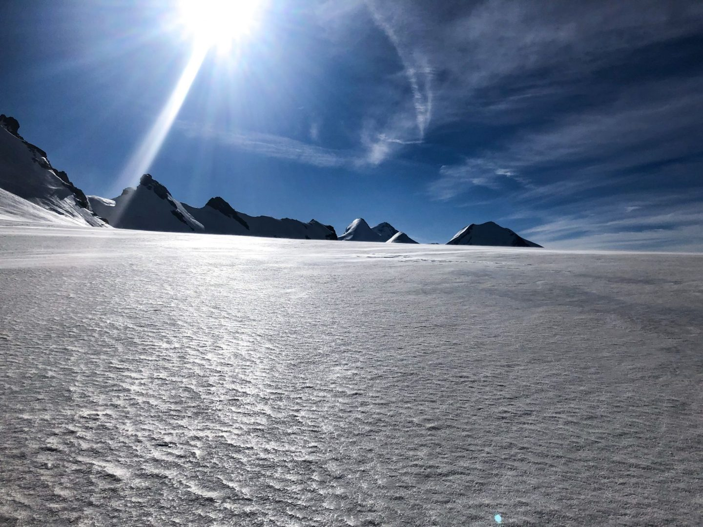 An expanse of snow with mountain peaks in the background and the sun reflecting off the glacier