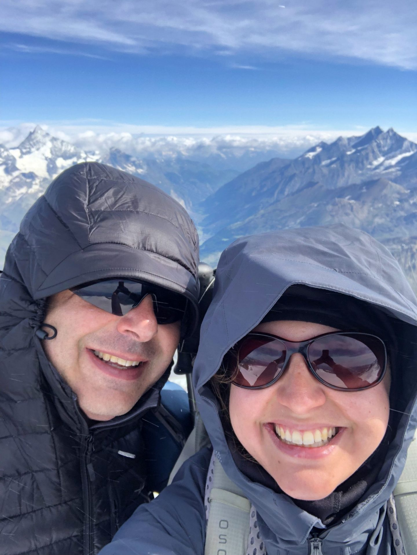 A selfie of Nell and her dad with sunglasses on and a thick coat with the hood up