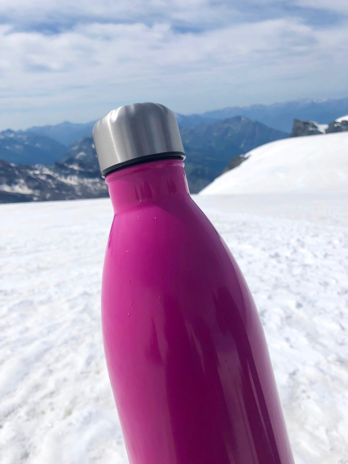 Pink water bottle on white snow when glacier hiking in the alps
