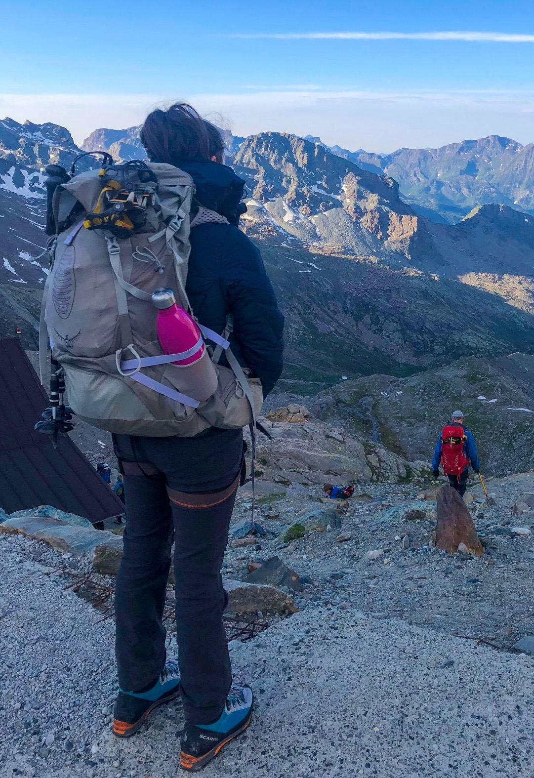 Girl looking out over mountain scenery, picture taken from behind. She is wearing an Osprey Aura Anti-Gravity rucksack with trekking poles attached, crampons sticking out the top and a pink water bottle in the side pocket. Glacier hiking alps.