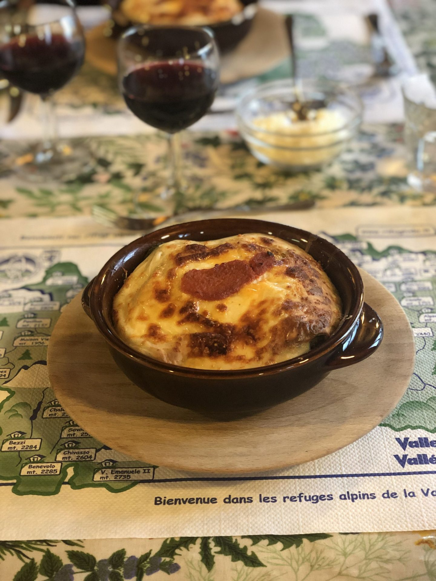 A bowl of cheesy cannelloni with a glass of red wine in the background, eaten in a mountain hut on the spaghetti tour