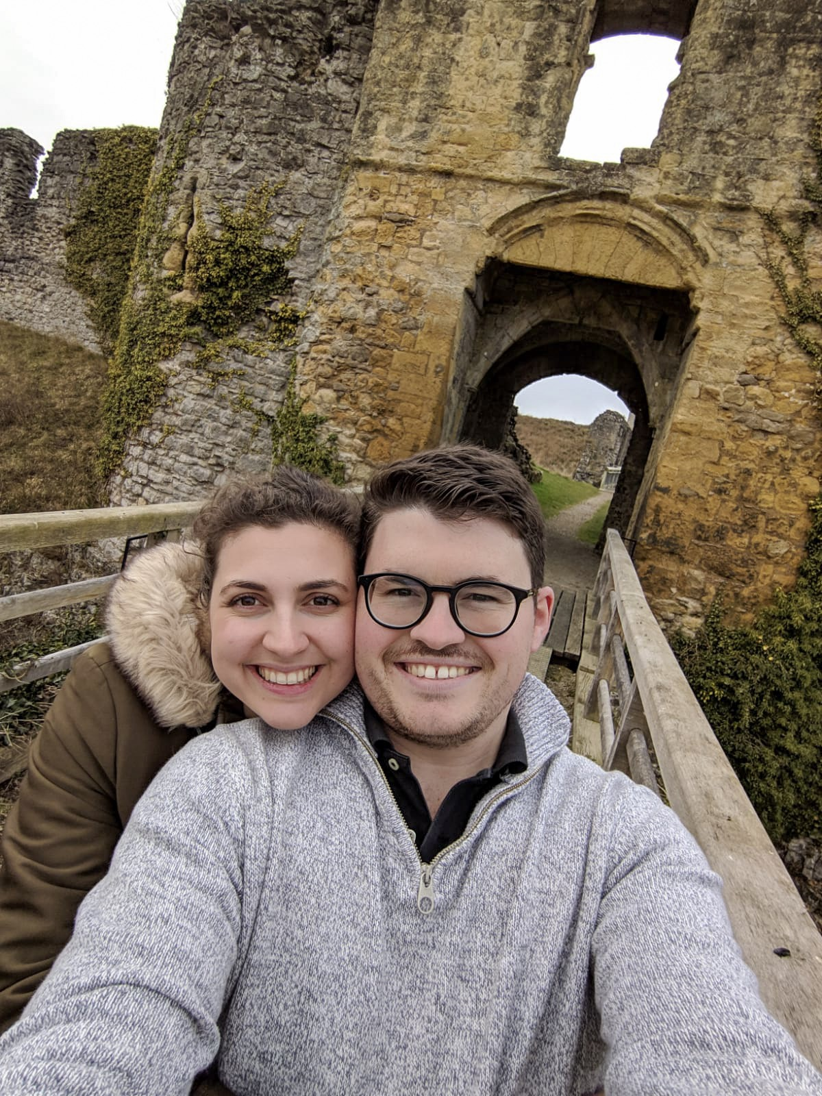 Selfie of man and woman looking directly into the camera, stood on the bridge at Helmsley Castle and smiling