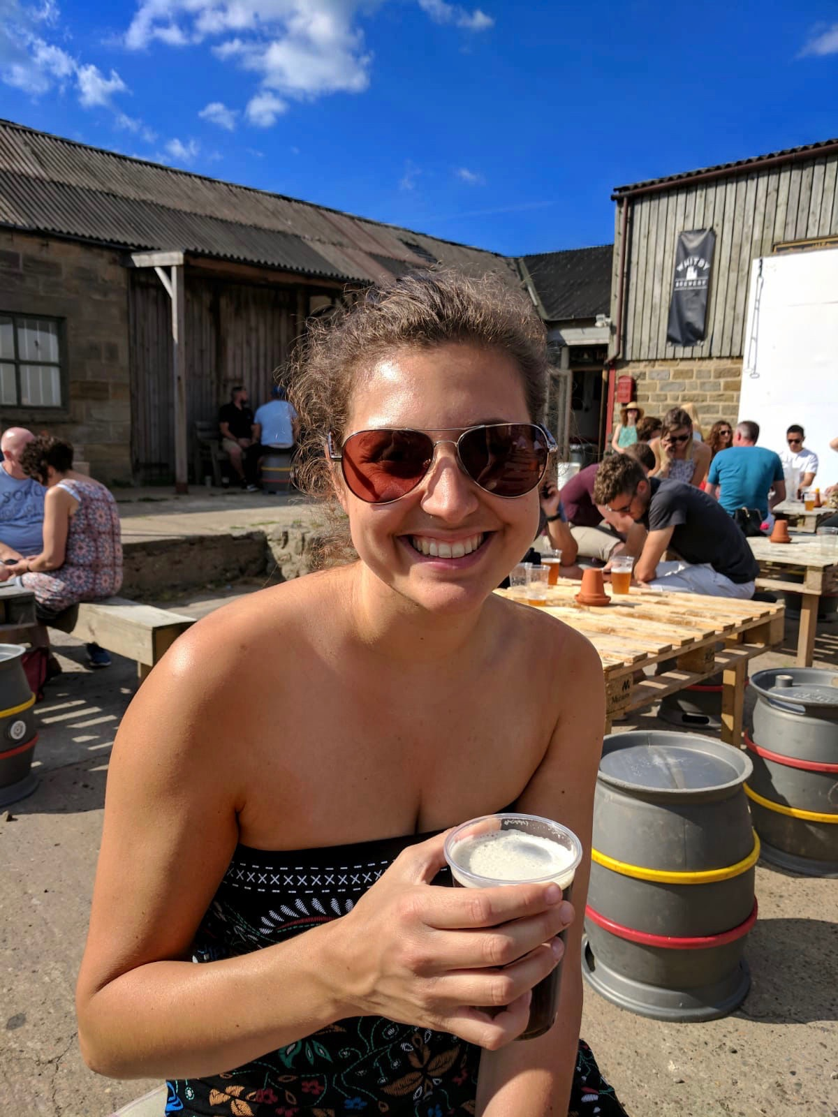 Girl sat outside Whitby Brewery with a pint of beer, wearing sunglasses and smiling at the camera.