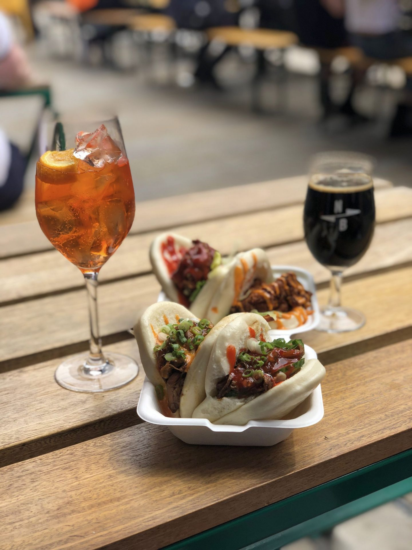 Places to eat in Leeds: an image for four bao buns on a wooden bench with an aperol spritz and a beer just out of focus behind