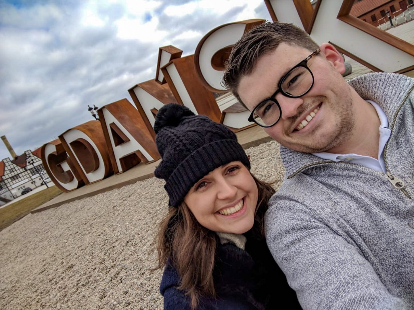 Couple smiling at the camera with giant Gdansk word behind them - cheap city break