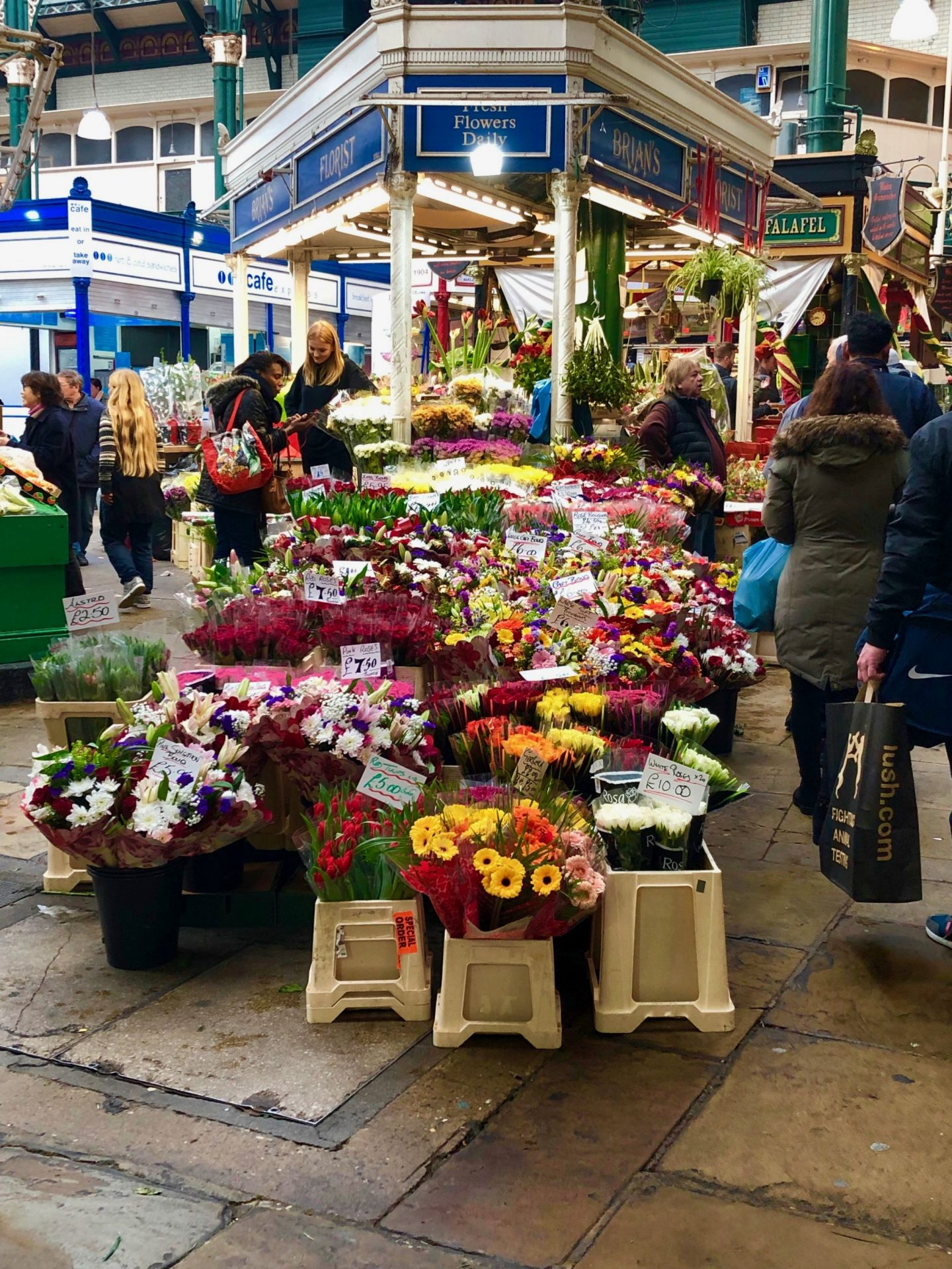 Leeds market: things to do in Leeds. A picture of a flower stall with shoppers browsing.