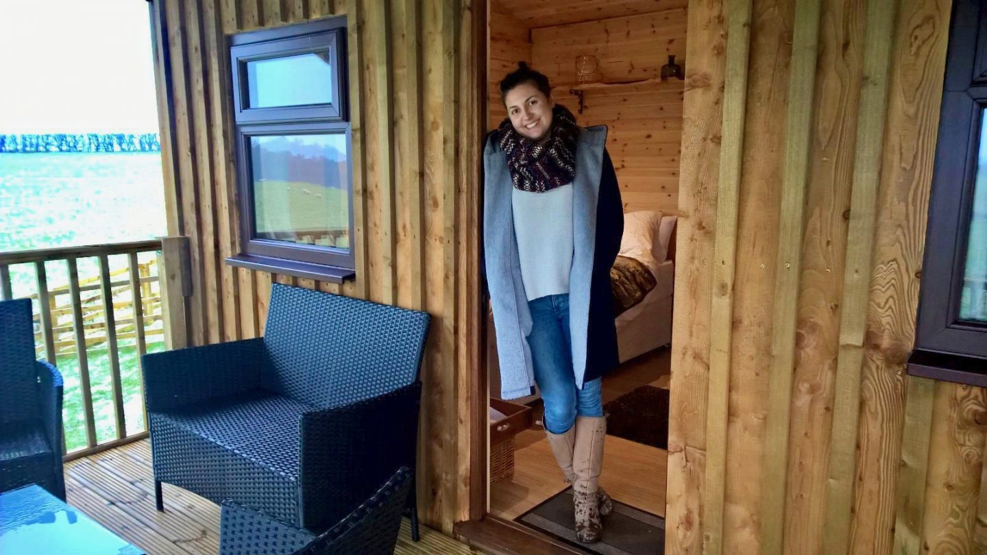 Girl stood in open doorway to Serendipity Shepherds Hut in Dalby Forest. She's leaning against the door and smiling at the camera.