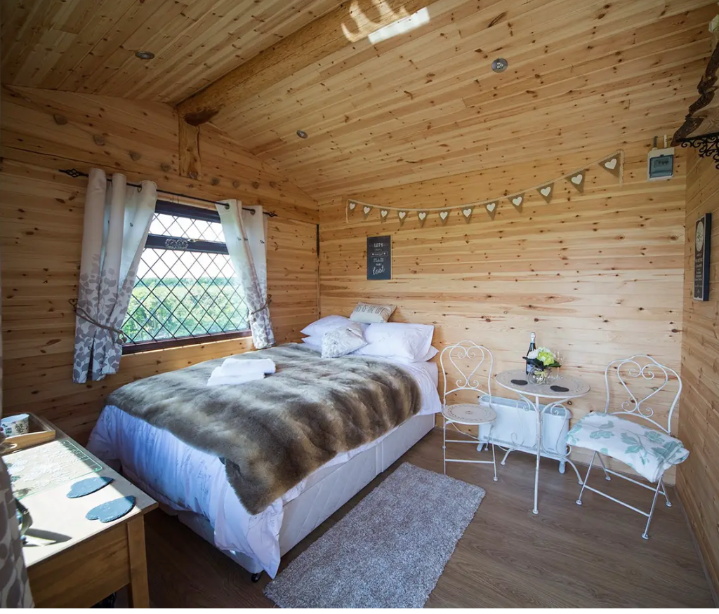 Inside Serendipity cabin in Dalby forest, showing a cosy king size bed with a faux fur through on top, a white bistro tables and chairs and bunting