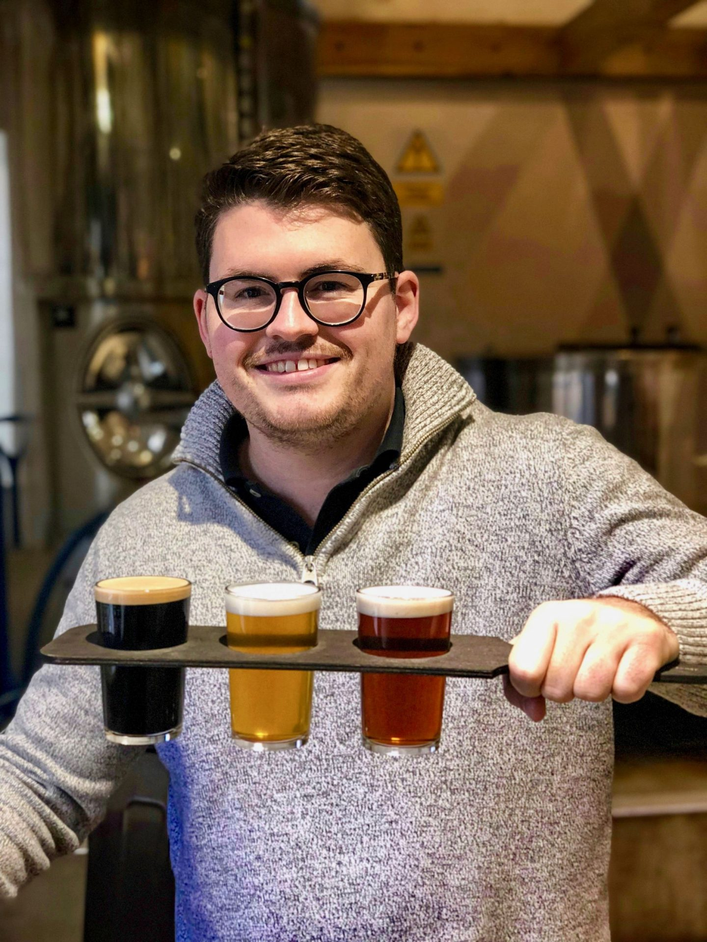 Things to do in Helmsley North Yorkshire: Nell's boyfriend holding a tasting flight of beer and looking very happy with himself