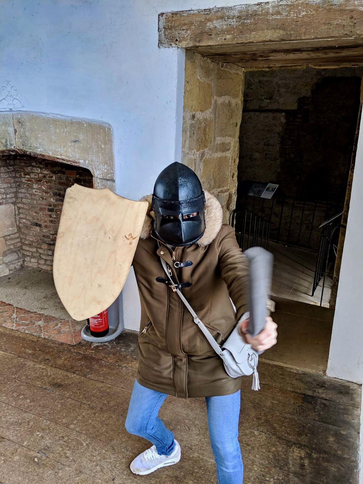 Things to do in Helmsley North Yorkshire: Nell wearing a plastic mask and holding a wooden shield inside Helmsley castle