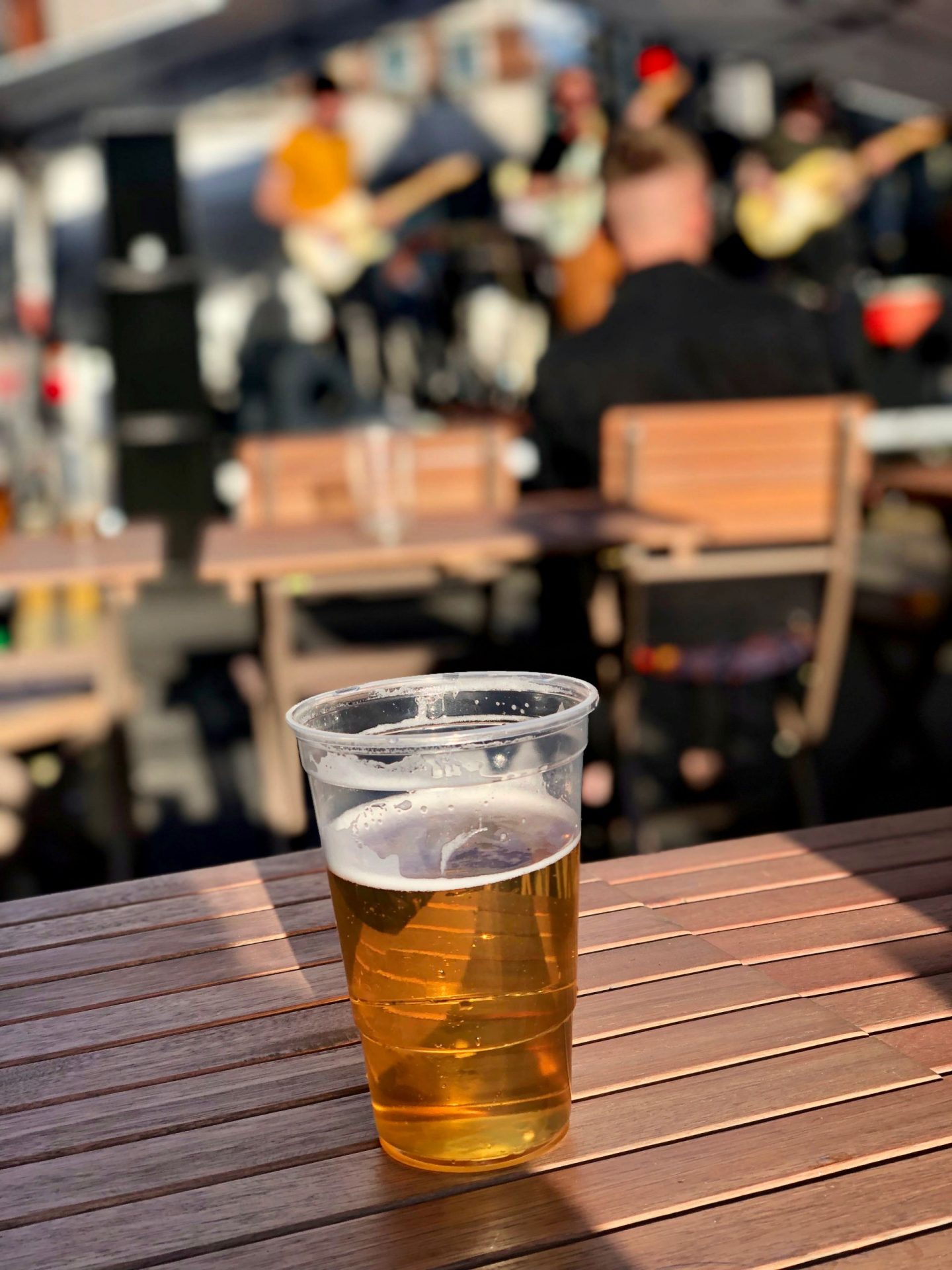 things to do in Leeds city centre - a pint of beer in a plastic cup on a wooden bench in a beer garden