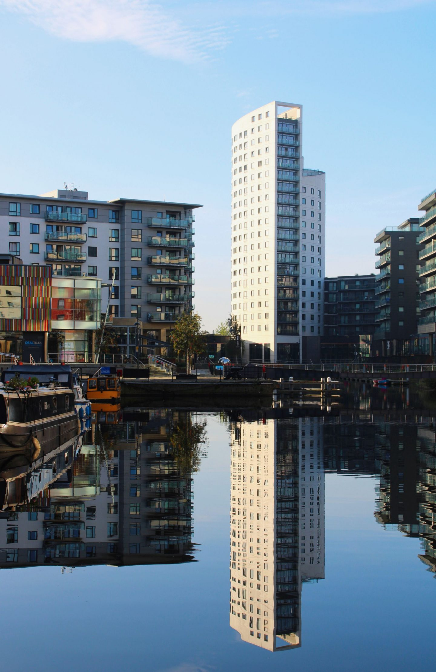 things to do in leeds city centre - sky scraper being reflected in the water at leeds dock, on a sunny day