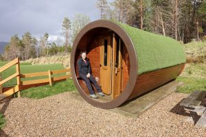 walking the west highland way accommodation: Hobbit house at Glencoe Mountain Resort when walking the west highland way. Nell is sat in the entrance to a wooden tube accommodation covered in green astroturf.