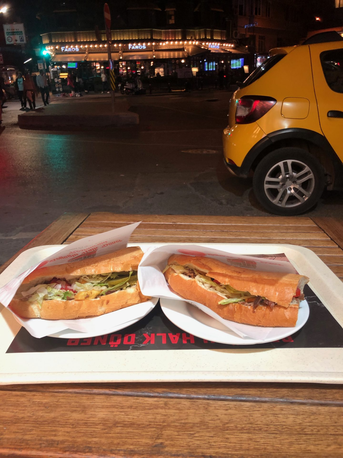 48 hours weekend in Istanbul: Two kebabs on a tray on a wooden table shot at night, with two yellow taxis blurred out in the background
