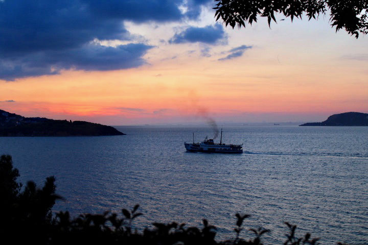48 hours weekend in istanbul: Sunset image from the princes islands. An orange sky is set against the ocean with two islands shown in black and a boat between them