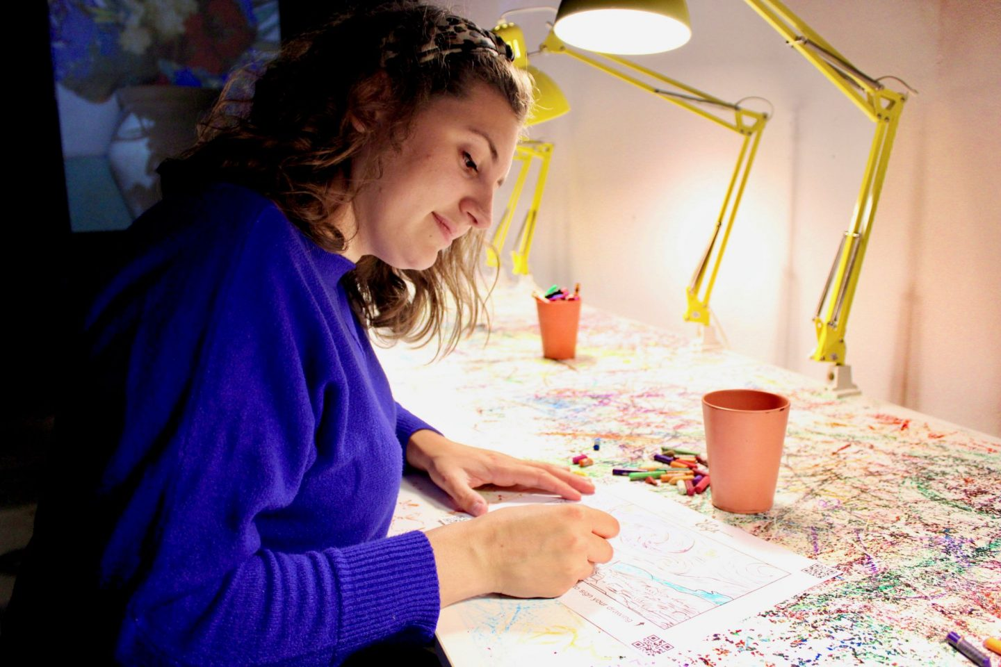 Girl concentrating on colouring in Van Gogh's Starry Night at the Van Gogh Immersive Experience in York. She's wearing a blue jumper and looking down at the drawing.