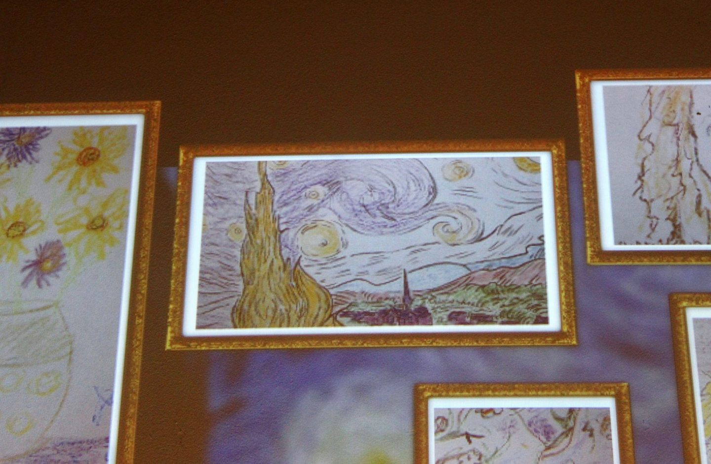 A picture frame showing a colouring in of Starry Night displayed on the wall at the Van Gogh immersive experience. The image doesn't use the traditional colours of Van Gogh's painting.