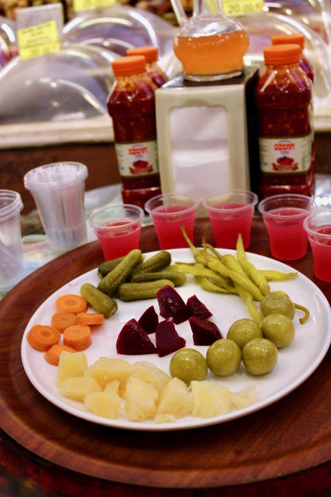 A plate of pickled vegetables and cups of bright pink pickle juice, tried in a pickle shop in istanbul