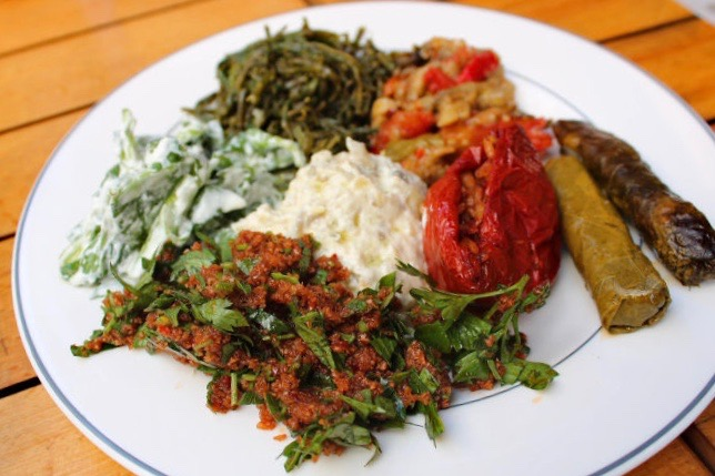 Mezze plate eaten in Istanbul. Colourful bulgar wheat, stuffed pepper, vine leaves, baba ganoush and vegetable dishes are served on a white place.