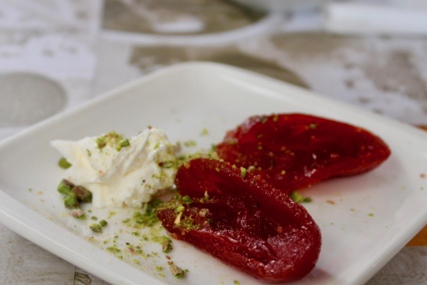 Two candied tomatoes served with cream and crushed pistachio on a white plate. Food to eat in Istanbul