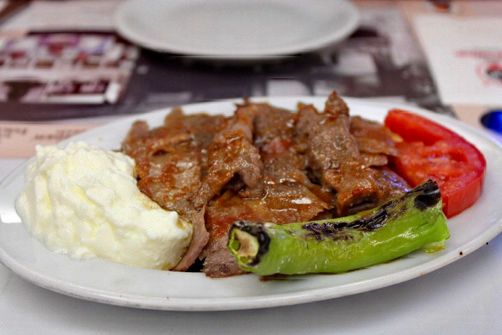 Iskender kebab, one of the foods to eat in Istanbul. Juicy meat is served with a grilled pepper on a plate and is covered in a shiny butter sauce.
