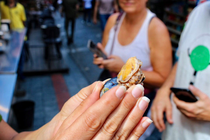 A close up on a mussel eaten in Istanbul held by a female hand.