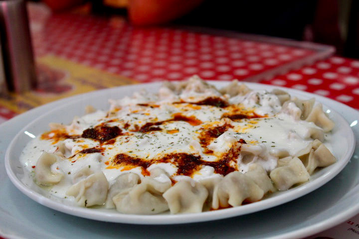 Manti dumplings in Istanbul. A close up of small dumplings with a sauce on top. served on a white plate with a red checked table cloth in the background.