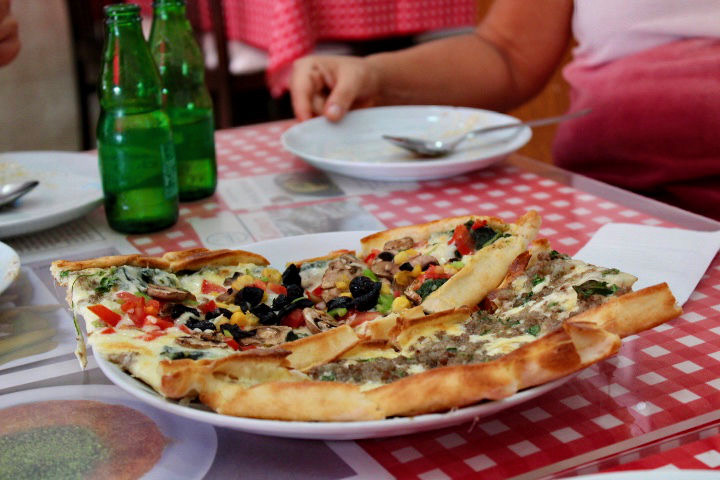 Pide eaten in Istanbul. Two different types are pictured on a white place with a red checked table cloth underneath