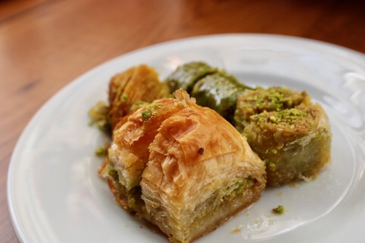 A close up of some bakalava eaten in Istanbul with flaky pastry and pistachio.