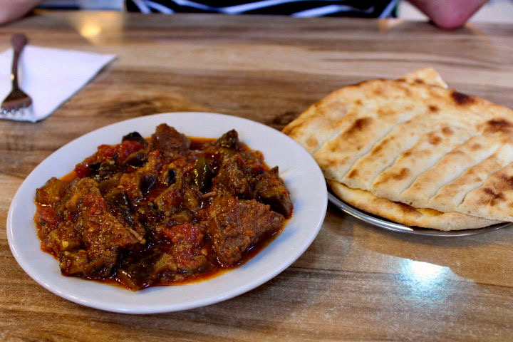 A bowl of lamb stew served on a white plate on a wooden table and accompanied by flatbread.