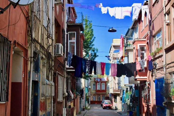 A colourful street in Balat with brightly coloured washing hanging from one colourful building to the next. 48 hours in Istanbul