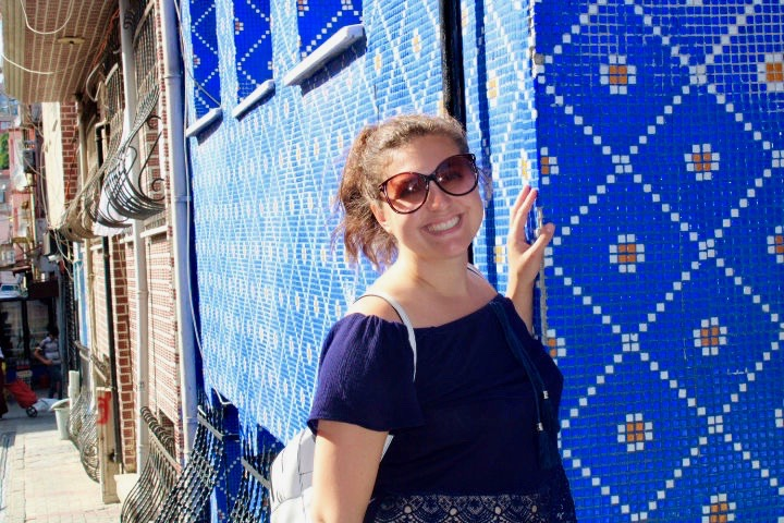 Girl standing next to a brightly coloured blue tiled wall. She has one hand on the wall and is smiling at the camera with her head tilted slightly back. 48 hours in Istanbul