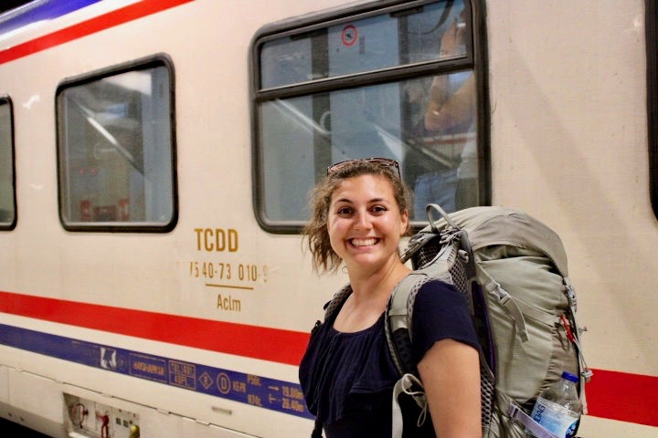 Girl stood outside Istanbul to Sofia night train wearing a backpack, she is smiling at the camera - balkan travel