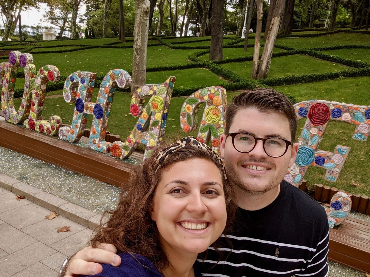A selfie of a couple in Gülhane Park with a sign of the park's name behind them. 48 hours in Istanbul