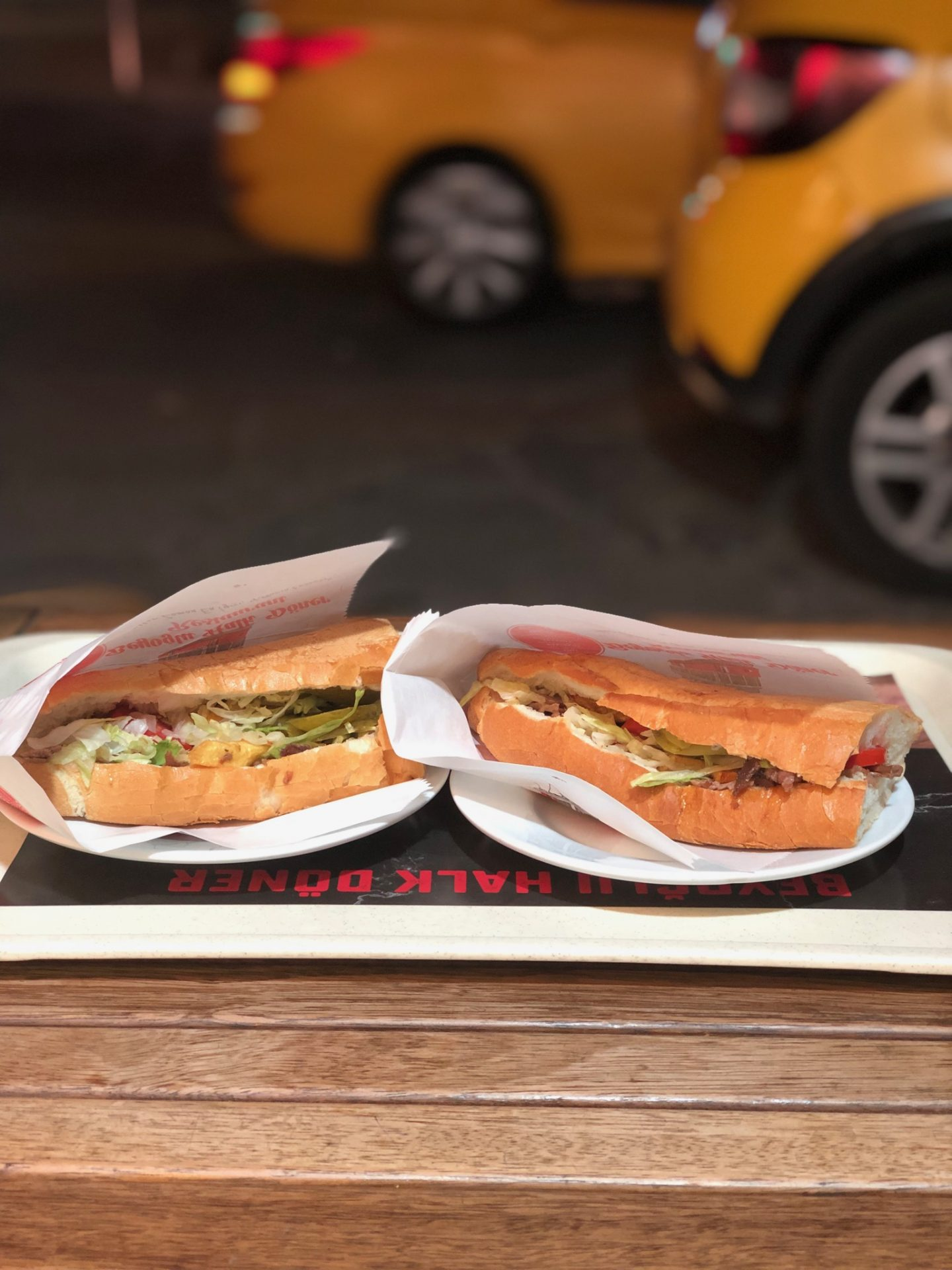 Two kebabs on a tray on a wooden table shot at night, with two yellow taxis blurred out in the background
