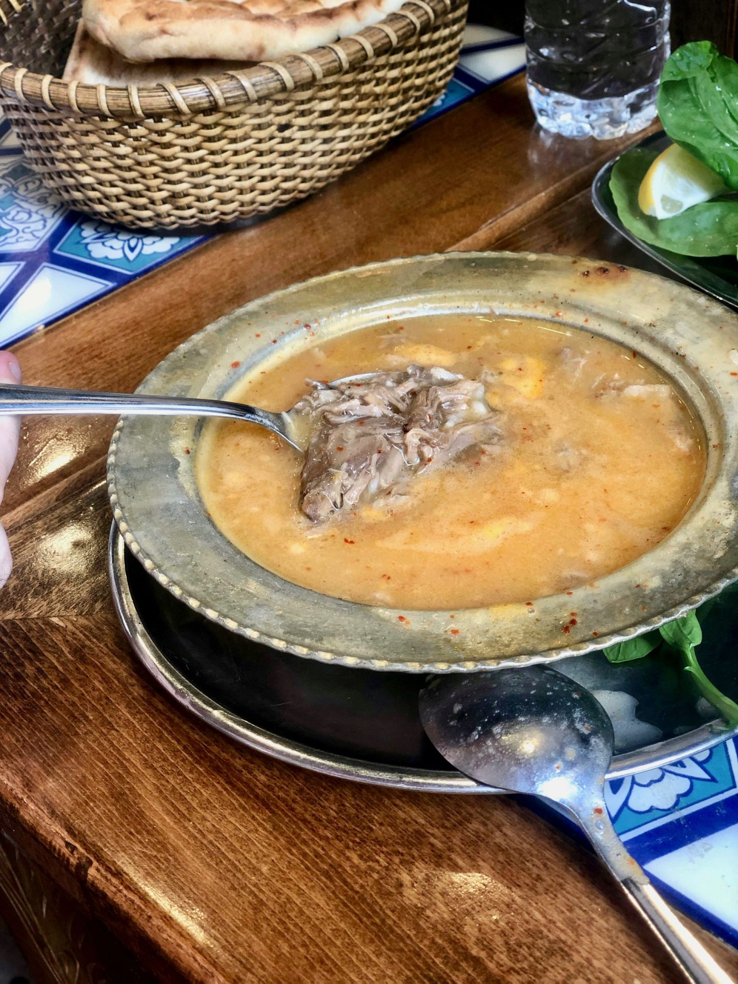 Beyran çorbasi - lamb soup. The soup is an orange colour and a spoon is holding up a chunk of lamb.