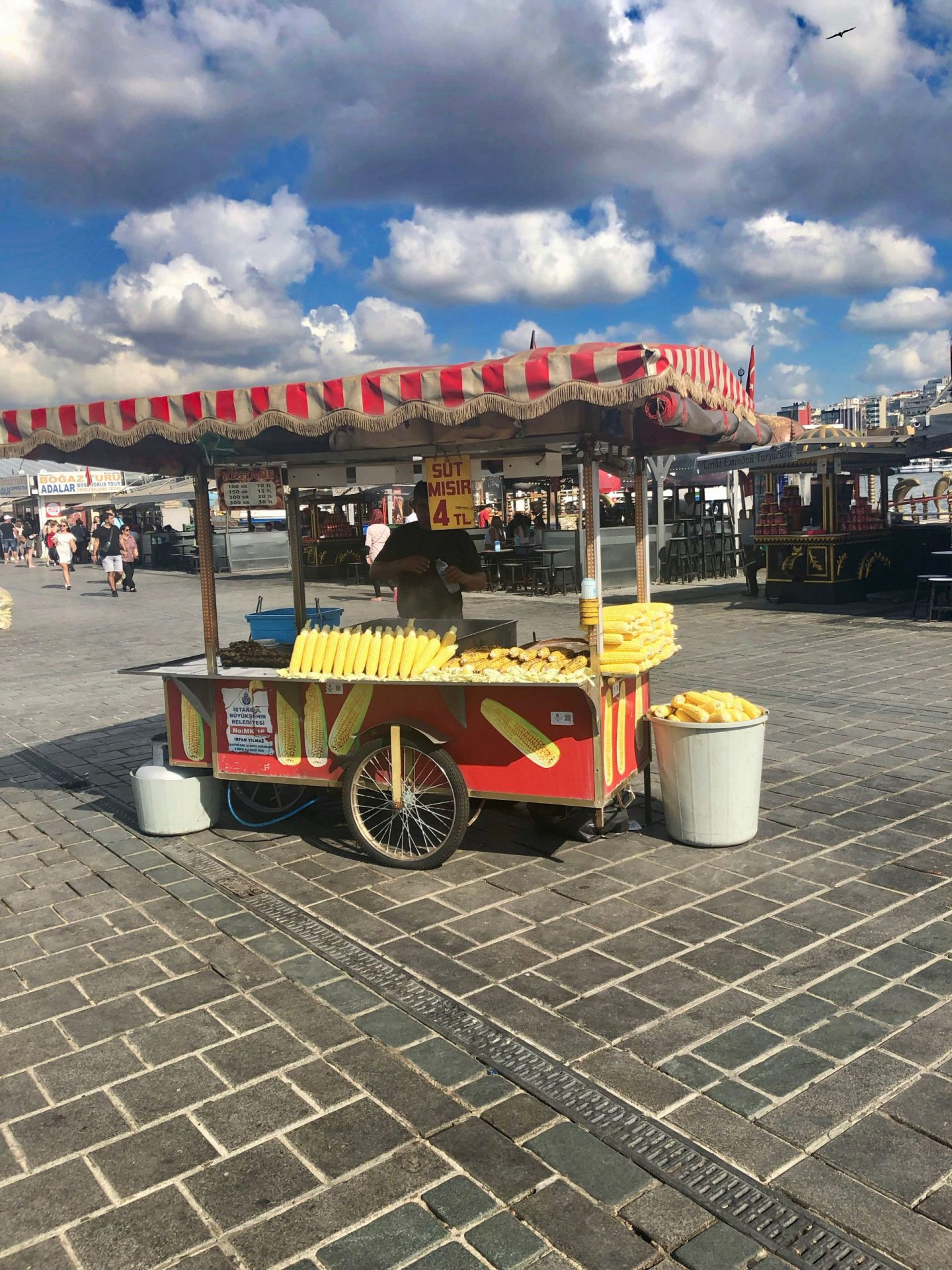 A corn on the cob cart in Istanbul, selling bright yellow corn. A blue sky with thick clouds dictates the background.