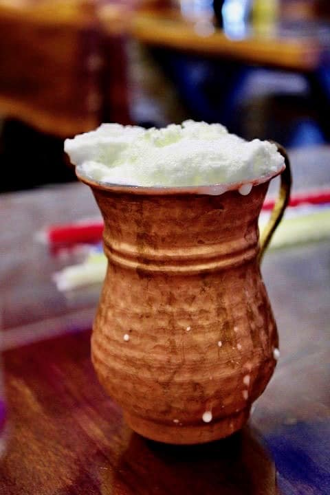 Turkish food in Istanbul: Ayran served in a copper jug. The ayran is in focus and the background is blurred out.