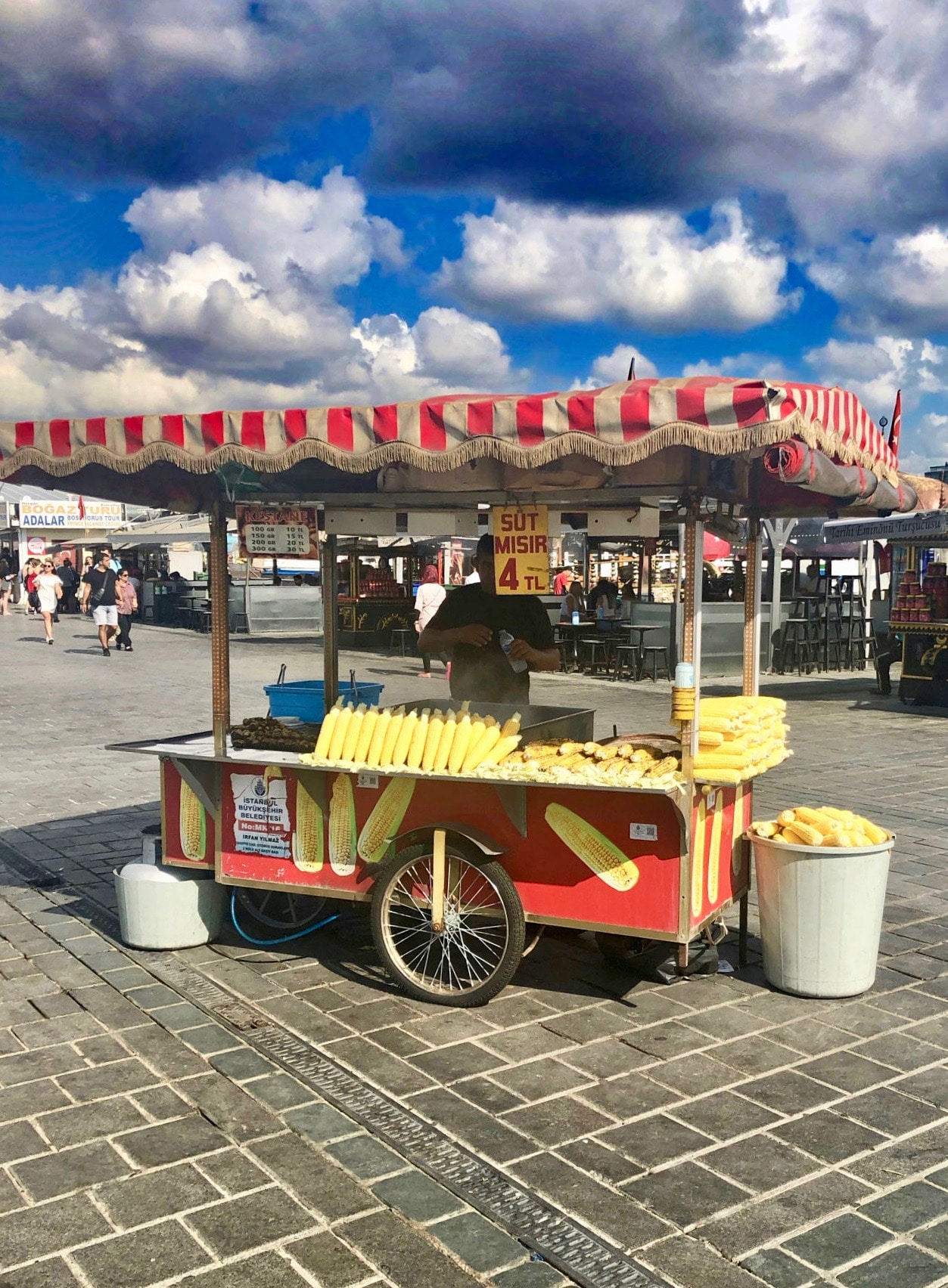 Turkish food in Istanbul: A corn on the cob cart in Istanbul, selling bright yellow corn. A blue sky with thick clouds dictates the background.